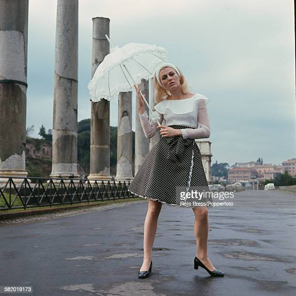 Sixties Fashion A young female model wears a cocktail skirt in black silk with white polka dots and a white organdy blouse whilst holding a white...