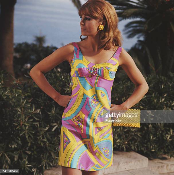 Sixties Fashion A young female model wears a Pucci style multicoloured beach dress with clutch bag in a Mediterranean setting circa 1968