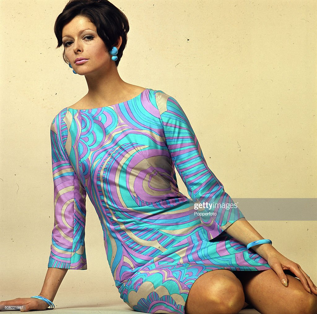 Sixties Fashion A young female model wears a Pucci style blue and pink patterned mini dress with matching earings circa 1966