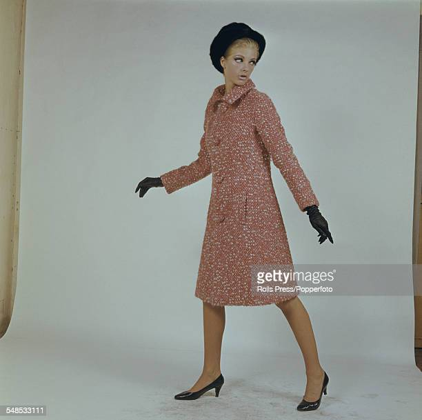 A young female model wears a red and grey mohair wool knee length coat with long sleeves shirt collar and four buttons on the front worn with a black...