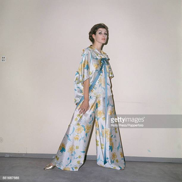 A young female model wears a sinuous all embracing two piece dress in white and blue orlon fabric with a floral motif comprising a extra wide legged...