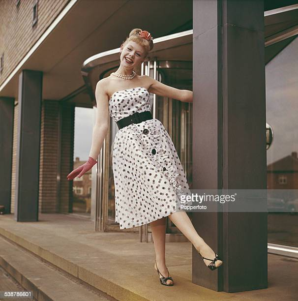 Sixties Fashion A young female model wears a strapless knee length polka dot dress with a black belt around her waist circa 1962