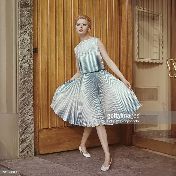 Sixties Fashion A young female model wears a twopiece ensemble in turquoise striped silk with the sleeveless bodice slightly draping on the front...