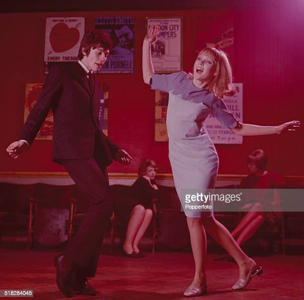 Sixties Fashion A young mod style couple dance together in a London nightclub circa 1965