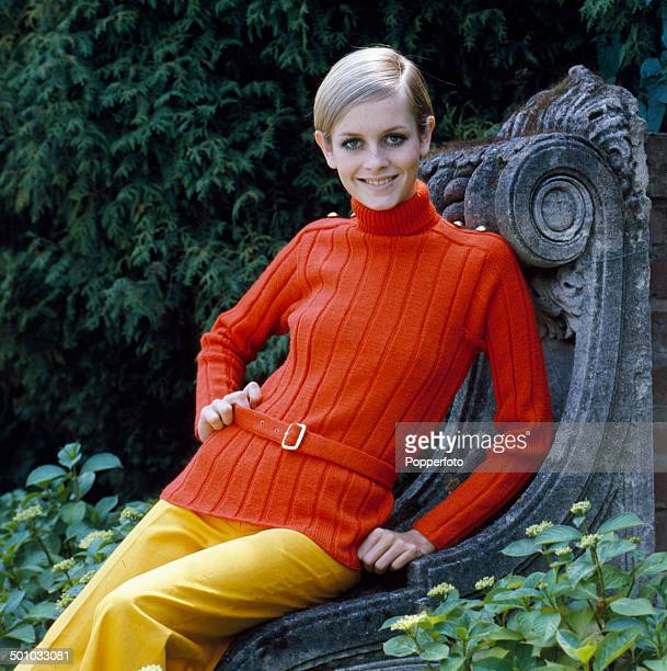 Sixties Fashion English model Twiggy poses wearing a knitted red sweater with military styling and yellow trousers in 1967