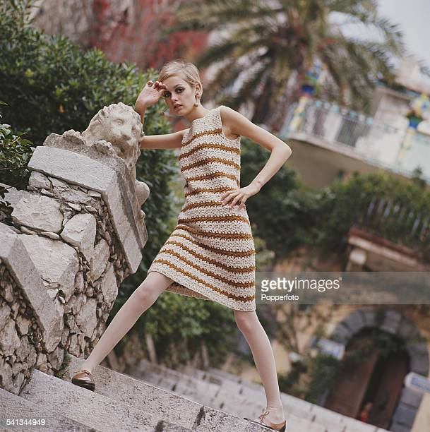 Sixties Fashion English model Twiggy wears a cream crochet dress with brown stripes and two tone brown shoes circa 1967