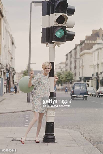 Sixties Fashion English model Twiggy wears a floral mini dress and holds a balloon next to a traffic light on the corner of Portobello Road and...