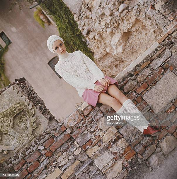Sixties Fashion English model Twiggy wears a white open knit sweater with matching hat and long socks with a short pink skirt and brown lace up shoes...