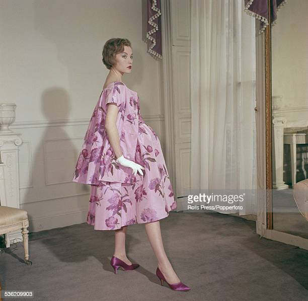 Sixties Fashion female model Susan Cox wears a short evening dress in purple chine taffeta with white gloves and matching shoes by fashion designer...