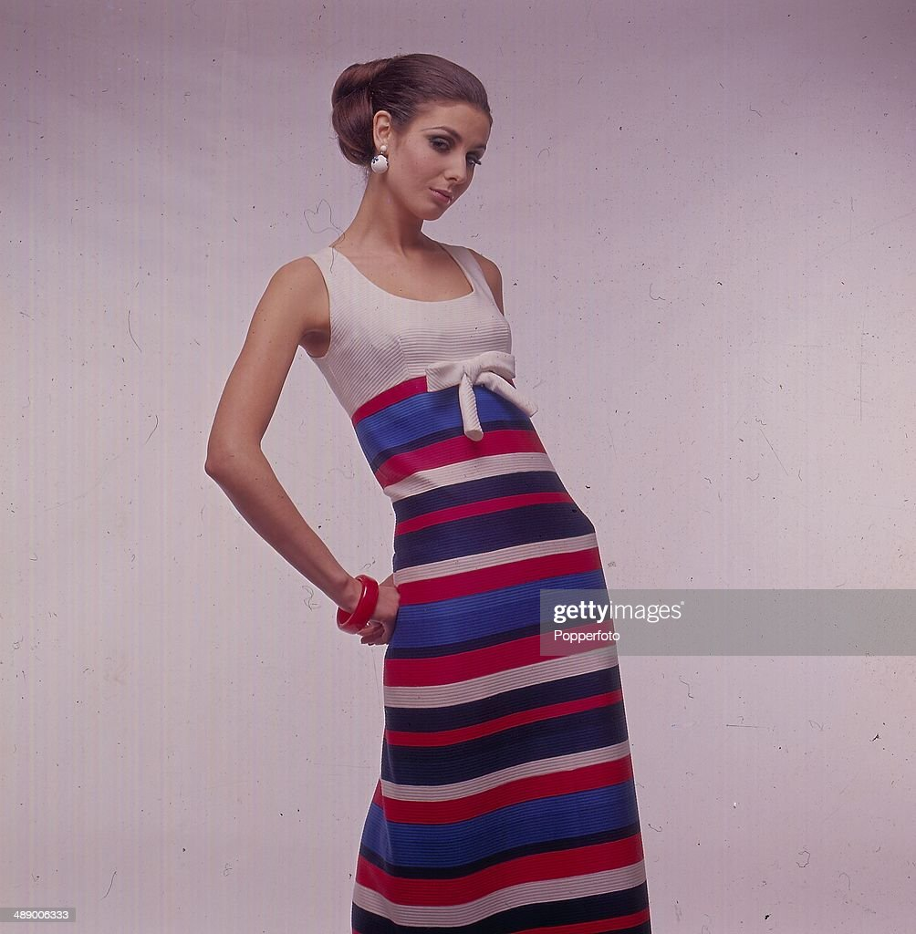 Sixties Fashion Portrait of a young woman wearing a full length striped empire line maxi dress with a bow at the front