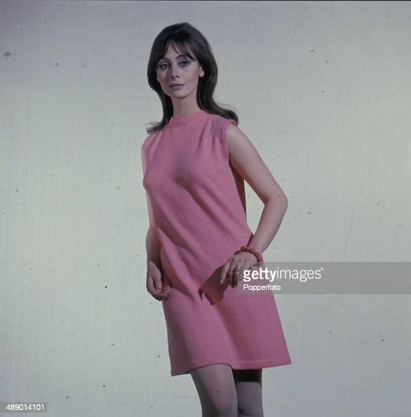 Sixties Fashion Studio shot of a young female model posing in a pink Aline shift dress