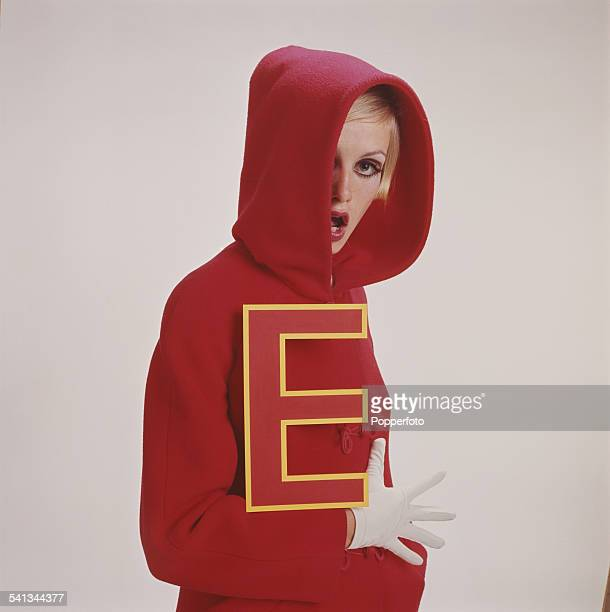 Sixties Fashion Twiggy models a red hooded jacket and white gloves whilst holding a large red letter 'E' circa 1966