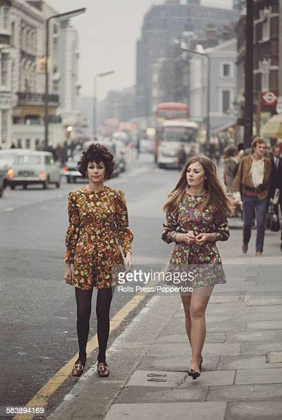 Sixties Fashion two young girls dressed in long sleeved floral print mini dresses walk along the Kings Road in Chelsea London in November 1967