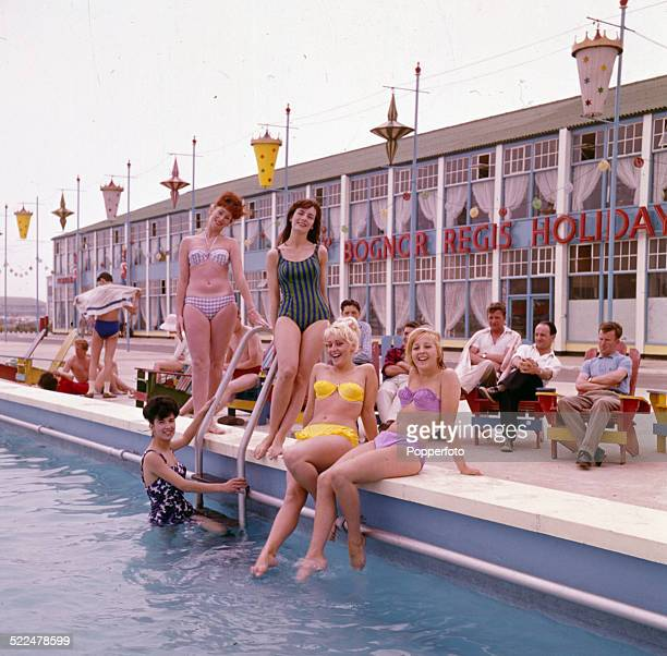 Sixties Fashion Young women wearing bikinis and swimming costumes pose beside the swimming pool at Butlins holiday resort in Bognor Regis England in...