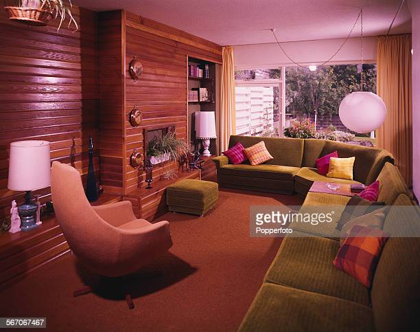 Sixties Interior Design View of the interior living room area of a modern house featuring matching corner sofa and ottoman in olive green with swivel...