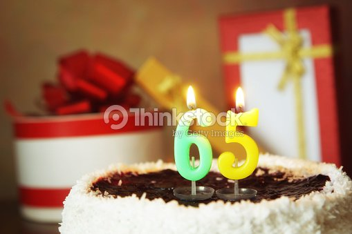 Sixty Five Years Birthday Cake With Burning Candles And Gifts Stock Photo