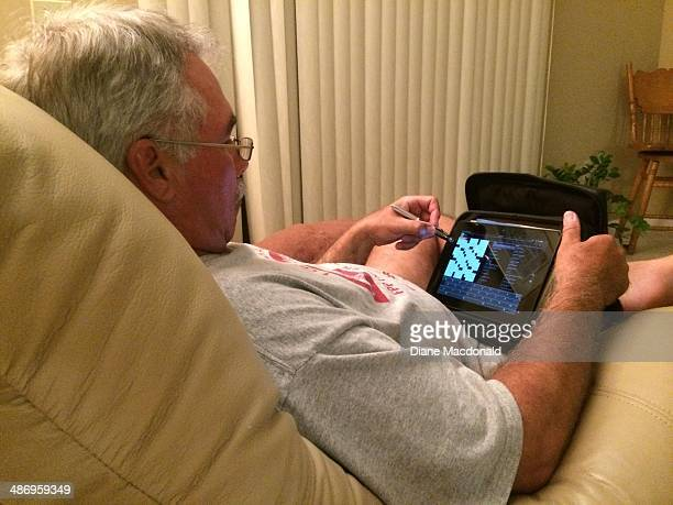 Sixty three year old senior man doing a crossword puzzle on a digital tablet