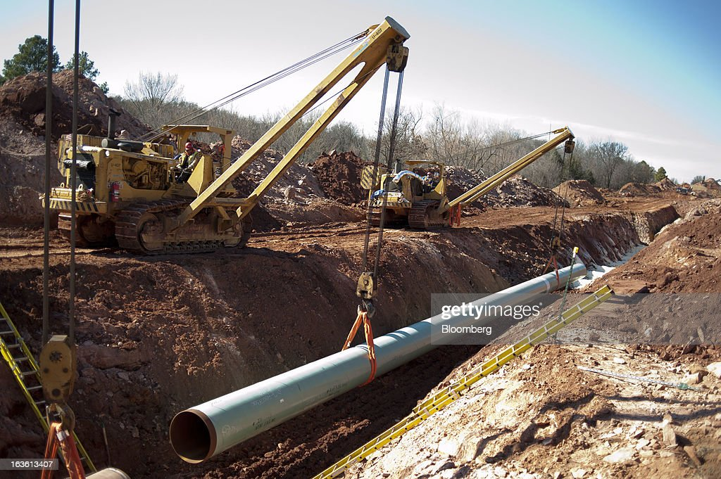 A sixty-foot section of pipe is lowered into a trench during construction of the Gulf Coast Project pipeline in Prague, Oklahoma, U.S., on Monday, March 11, 2013. The Gulf Coast Project, a 485-mile crude oil pipeline being constructed by TransCanada Corp., is part of the Keystone XL Pipeline Project and will run from Cushing, Oklahoma to Nederland, Texas. Photographer: Daniel Acker/Bloomberg via Getty Images