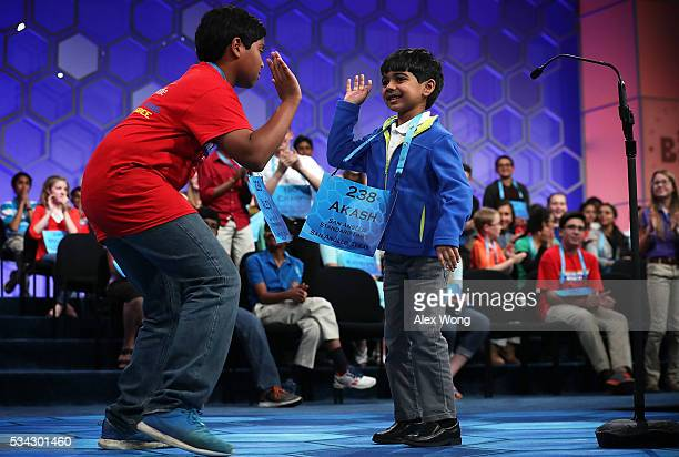 Sixyearold Akash Vukoti of San Angelo Texas hifives Alex Iyer of San Antonio Texas as he leaves the stage after he misspelled his word in round three...