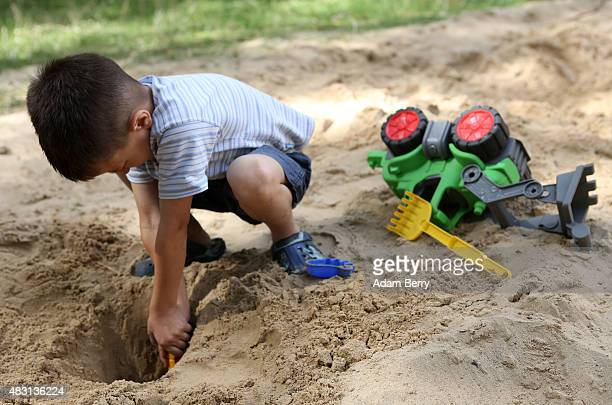Sixyearold Bosnian refugee Dini plays in a sandbox at a temporary home providing assistance for refugees on August 6 2015 in the Gatow district of...