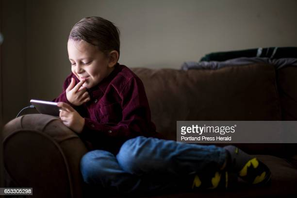 Sixyearold Brock Chadwick who was recently diagnosed with a rare form of brain cancer smiles as he watches a video while lounging in the living room...