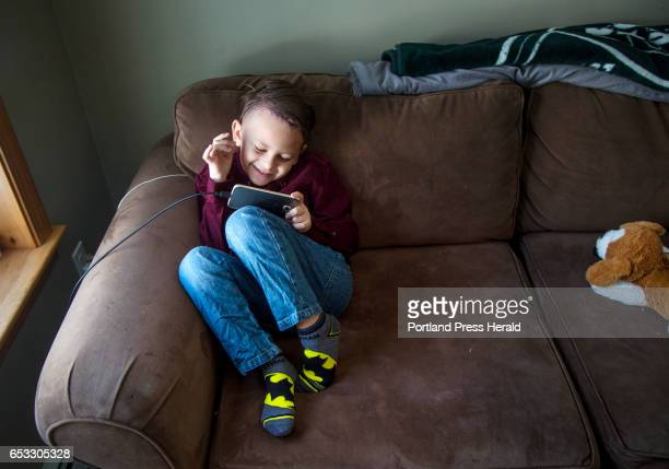 Sixyearold Brock Chadwick who was recently diagnosed with a rare form of brain cancer laughs as he watches a video while lounging in the living room...