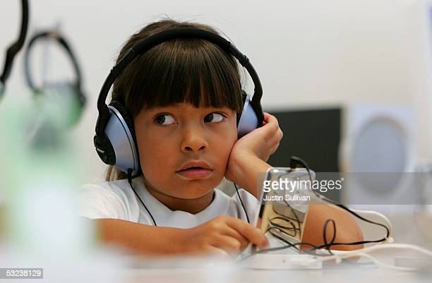 Sixyearold Emma Cordell listens to a new iPod on display at the Apple Store July 14 2005 in San Francisco California Shares of Apple Computer surged...