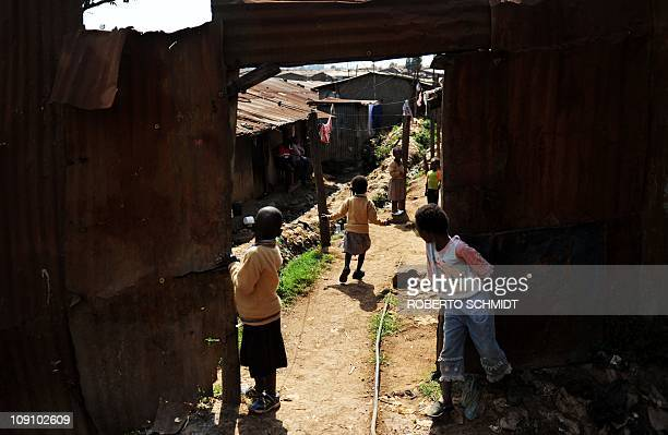 Sixyearold Joan Achieng runs while playing in front of her home in Kibera one of Africa's largest slums on November 29 2010 Both Joan and Beckham...