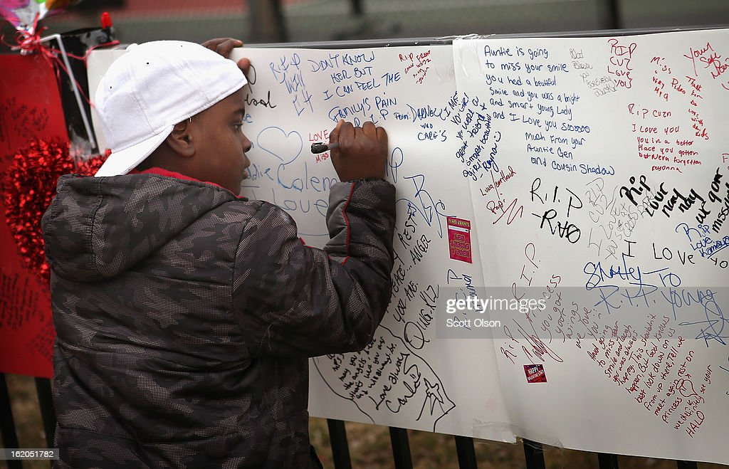 Six-year-old Ray Myles signs a memorial to his eighteen-year-old cousin Frances Colon near the spot where she was murdered on February 18, 2013 in Chicago, Illinois. Colon, who was shot February 15th while walking by a neighborhood play lot, was the 51st person murdered in Chicago in 2013. She was the third student from Roberto Clemente High School, a Westside school with less than 800 students, to be murdered in the past three months.