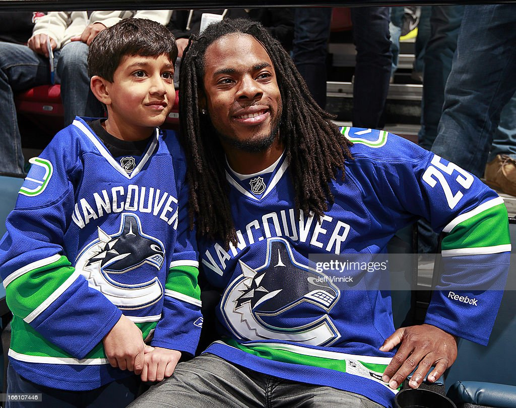 Six-year-old Tage Poon gets his picture taken with Richard Sherman of the NFL Seattle Seahawks during the NHL game between the Vancouver Canucks and the Phoenix Coyotes at Rogers Arena April 8, 2013 in Vancouver, British Columbia, Canada.
