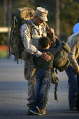 Sixyearold Tyler holds onto his father Gunnery Sgt Willy Ellerbrock as Marines and sailors of the 1st Marine Logistics Group return home from a...