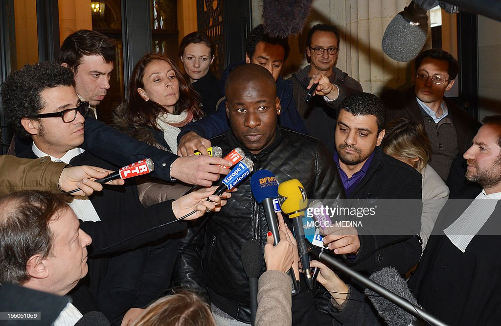 Siyakha Traore (C), Bouna's elder brother, beside the president of French association 'Au dela des mots' (Beyond words) Samir Mihi (C,R), answers journalists' questions as he leaves the Cour of Cassation, France's highest court, in Paris on October 31, 2012, after the court cancelled a previous dismissal in the case of the two police officers involved in the death of Bouna Traore and Zyed Benna in 2005. These two French teenagers of African origin died on October 27, 2005, after being electrocuted in a sub-station while fleeing from the police. The death of the two boys started the country's worst urban unrest since the 1968 student revolts. The lawyers of the Traore and Benna families are seen at left, Jean-Pierre Mignard (L, down) and Emmanuel Tordjman (L, up) and at right, Patrice Spinosi. AFP PHOTO / MIGUEL MEDINA