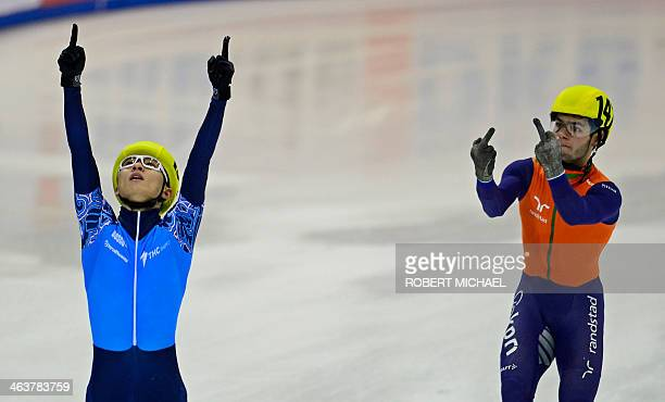 Sjinkie Knegt of the Netherlands' team gestures next to Victor An of the team of Russia celebrating after Russia won the men's 5000m relay final race...