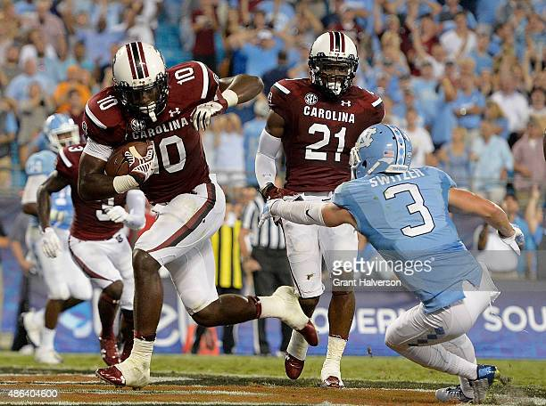 Skai Moore of the South Carolina Gamecocks intercepts a pass intended for Ryan Switzer of the North Carolina Tar Heels late in the fourth quarter of...