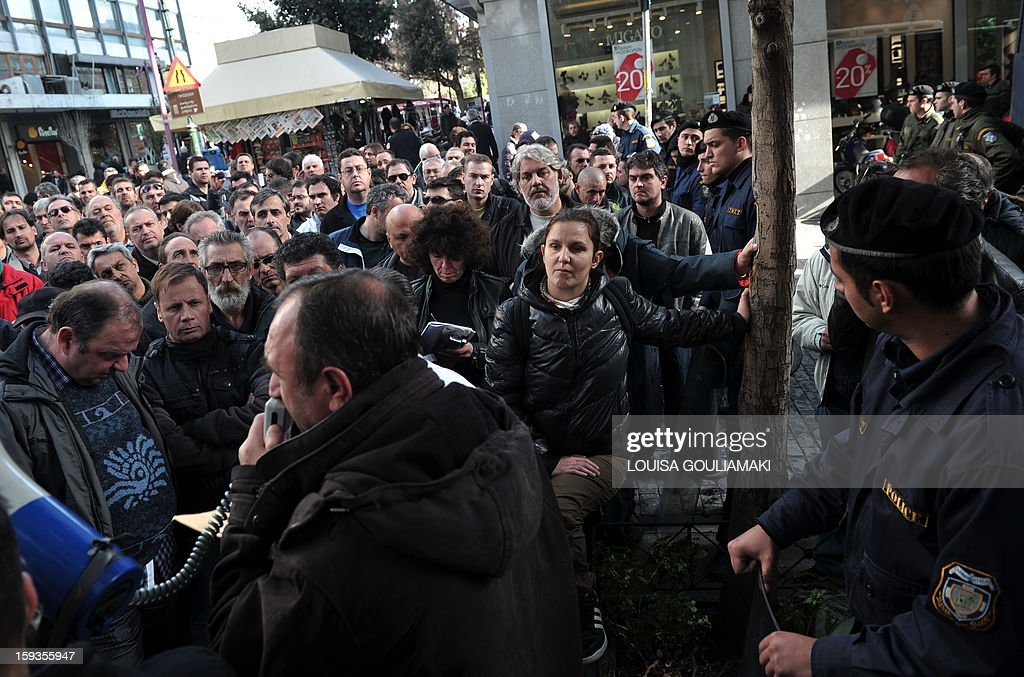 Skaramangas shipyard's workers listen to a unionist outside the Finance Ministry in Athens after meeting with ministry offficials over payments delays and the imposed rotation work one day per week on January 11, 2013. Workers at Skaramangas are on industrial action for months over backpays from the private Arab-German consortium which controls the shipyards since 2010.
