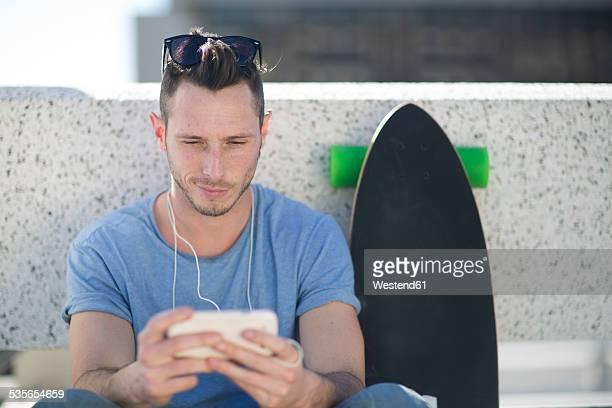 Skate boarder having a break using his smartphone