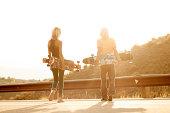 Skateboard friends walking down the street.