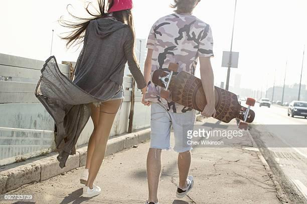 Skateboarder couple walking on street, Budapest, Hungary