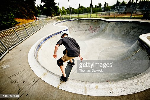 Skateboarder dropping into bowl of skate park : Stock Photo