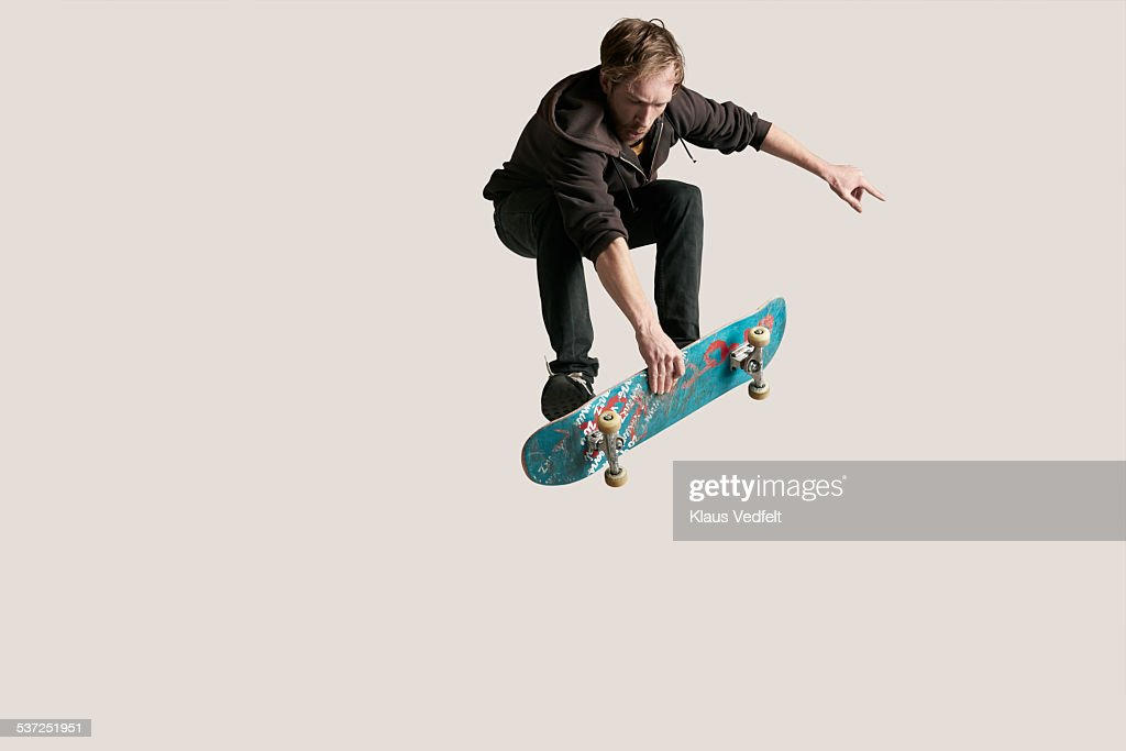 Skateboarder grabbing board in the air