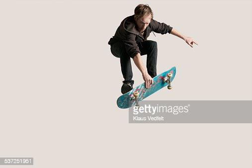Skateboarder grabbing board in the air