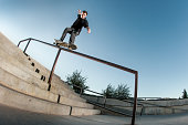 Skateboarder grinding a hand rail.