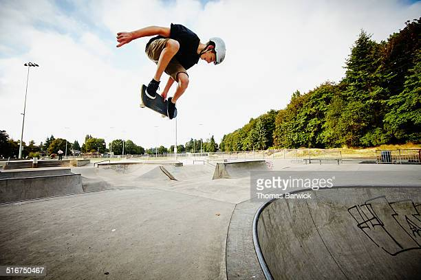 Skateboarder in mid air in skate park