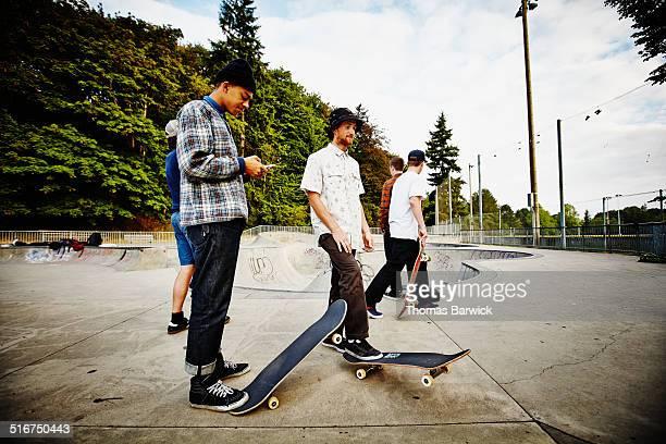 Skateboarder in skate park looking at smartphone