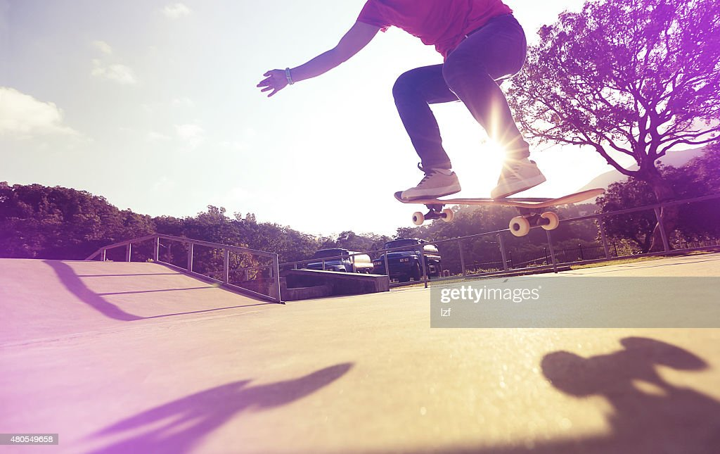 skateboarder legs doing a trick ollie at skatepark : Stock Photo