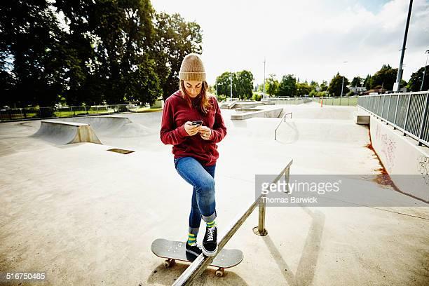 Skateboarder looking at smartphone in skate park