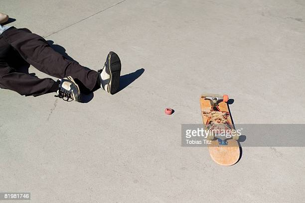 A skateboarder lying on the floor next to a broken skateboard