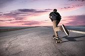 Skateboarder pushing on a concrete pavement along the harbour during the sunset.