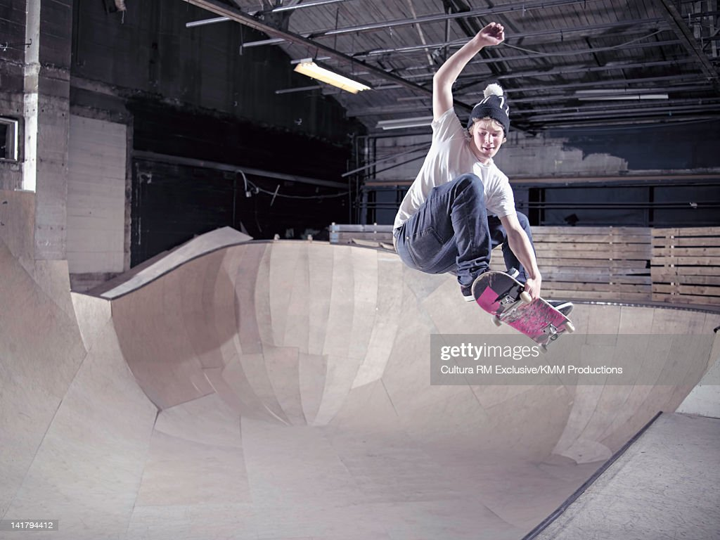 Skateboarder skating on indoor ramp : Stock Photo