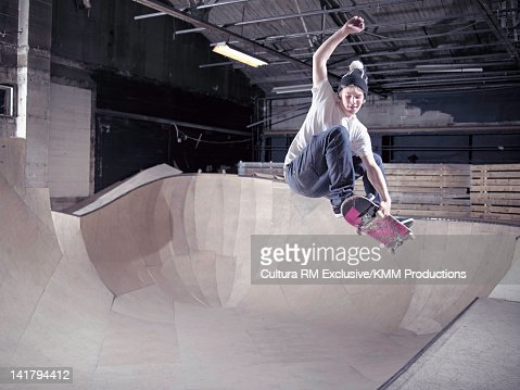 Skateboarder skating on indoor ramp : Stockfoto